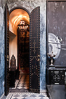 Double-height, narrow studded double doors lead from the living room of The Blue Suite into the corridor atmospherically lit with Moroccan lanterns