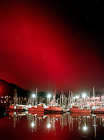 Intense red northern lights flare over Harris Harbor in Juneau, Alaska. ?&acirc;