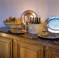 Large pewter platters and ceramic bowls filled with bottles and corn husks stand on the marble surface of a sideboard