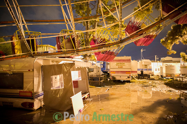 View of the wreckage of a fair ride leaning on a tree after a tornado ripped through a funfair in Gandia, near Valencia on September 29, 2012.  At least eight people, including a young girl and an elderly woman, have died in Spain as a result of floods brought on by downpours, regional officials said. Four people died in the Andalusia region, including a woman in her 80s, a couple found in their car and a man who died of a heart attack. Some 500 people remained evacuated from their homes in the area early on Saturday after the torrential rains caused rivers to break their banks and flooded roads and railways, regional authorities said. (c) Pedro ARMESTRE
