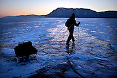 Heleen treks across frozen Lake Baikal in Siberia, Russia, towards the Olkhon Island. (Second night). .They are a group of five people: Justin Jin (Chinese-British), Heleen van Geest (Dutch), Nastya and Misha Martynov (Russian) and their Russian guide Arkady. .They pulled their sledges 80 km across the world's deepest lake, taking a break on Olkhon Island. They slept two nights on the ice in -15c. .Baikal, the world's largest lake by volume, contains one-fifth of the earth's fresh water and plunges to a depth of 1,637 metres..The lake is frozen from November to April, allowing people to cross by cars and lorries.