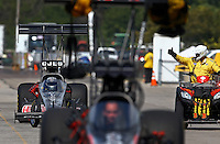 Sep 28, 2013; Madison, IL, USA; NHRA top fuel dragster driver Bob Vandergriff Jr (left) is signaled by a member of the safety safari during qualifying for the Midwest Nationals at Gateway Motorsports Park. Mandatory Credit: Mark J. Rebilas-