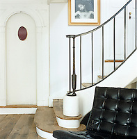 A sweeping staircase with plain wrought-iron banisters descends to the open plan living area furnished with Barcelona chairs