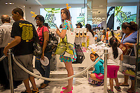 """Shoppers on line at the grand opening of the H&M Fifth Avenue department store in New York on Thursday, July 17, 2014. The store is the largest H&M with 57,000 square feet and to celebrate the opening Hennes & Mauritz has tied in with the artist Jeff Koons for a limited edition handbag with Koons' iconic """"Balloon Dog (Yellow)"""" printed on it. Koons currently has a retrospective at the Whitney Museum as well as his """"split-Rocker"""" on display a few blocks away in Rockefeller Center. While H&M has had numerous collaborations with designers, this is the first time they have worked with a major artist, albeit an artist that embraces the commercial aspects of fine art.    (© Richard B. Levine)"""