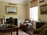 The comfortable study is furnished with a mixture of leather armchairs grouped around a mahogany work table