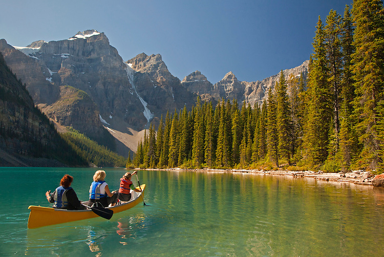 Three women canoeing on Moraine Lake, Banff National Park, Alberta, Canada