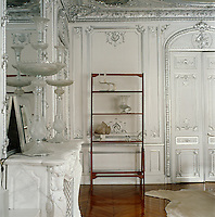 "In the living room of this Paris apartment the mouldings of the elaborate panelling have all been picked out in silver leaf and the walls have been painted in a shade called ""Not Totally White"""