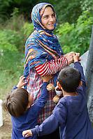 SERBIEN, 08.2016, Kelebija. Internationale Fluechtlingskrise: An der mit Zaeunen abgesperrten ungarischen Grenze stauen sich Fluechtlinge und Migranten. Sie bitten meist vergebens um Einlass in die  Asyl- und Transitzonen (blaue Container). So haben sich auf serbischer Seite provisorische Lager mit sehr schlechten Bedingungen gebildet. | International refugee crisis: Refugees and migrants have been piling up at the fenced-off Hungarian border. They are waiting for entrance into the asylum and transit zones (blue containers), mostly in vain. Thus provisional camps have emerged on the Serbian side with very bad conditions. In the picture Noor Mahmud with her sons Ali and Achmed.<br /> &copy; Szilard V&ouml;r&ouml;s/EST&amp;OST