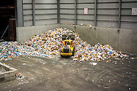 A front loader moves mountains of trash in the tipping area from the city's curbside recycling program at the Sims Municipal Recycling facility in Sunset Park in Brooklyn in New York on Tuesday, September 30, 2014. Opened in 2013 the state-of-the-art facility processes the majority of the city's commingled curbside recyclables. (© Richard B. Levine)