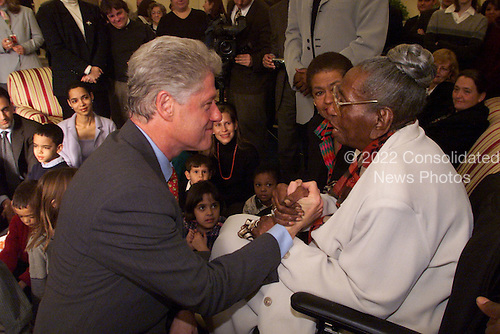 United States President Bill Clinton greets 100-year-old Charlotte Filmore in the Oval Office of the White House in Washington, D.C. on January 15, 2000. Ms. Filmore joined the President for the broadcast of his weekly radio address. Seated next to Ms. Filmore is Congresswoman Eleanor Holmes Norton (Democrat of the District of Columbia)..Credit: White House via CNP