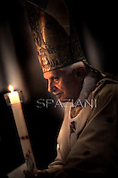 Pope Benedict XVI holds a candle during the Easter vigil mass in Saint Peter's Basilica, in the Vatican...7 April 2012.. .