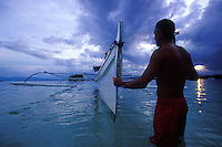 Traveler at bow of local outrigger canoe at sunset, southern Philippines