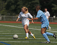 Boston Aztec midfielder Riley Houle (22) on the attack.  In a Women's Premier Soccer League (WPSL) match, Boston Aztec (white) defeated Seacoast United Mariners (blue), 2-1, at North Reading High School Stadium on Arthur J. Kenney Athletic Field on on June 23, 2013. Due to injuries through the season, Seacoast United Mariners could only field 10 players.