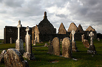 Low angle view of  Gravestones, Temple Doolin or Dowling, 10th century, restored 1689, and Temple Hurpan, 17th century, and in the distance, Clonmacnoise Cathedral, 10th century, Clonmacnoise, County Offaly, Ireland, in the evening. Clonmacnoise was founded by St Ciaran, with the help of Diarmait Ui Cerbaill, Ireland's first Christian King. The site presents the largest collection of Early Christian graveslabs in Western Europe. Picture by Manuel Cohen