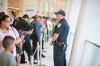 A Port Authority Police Office stands guard in the World Trade Center Transportation Hub, known as the Oculus, on Tuesday, August 16, 2016 during the grand opening of the retail spaces. The 350,000 square foot retail space will feature over 100 stores when they all open, including a now opened Apple Store. The mall opens almost 15 years after the World Trade Center terrorist attack.  (© Richard B. Levine)