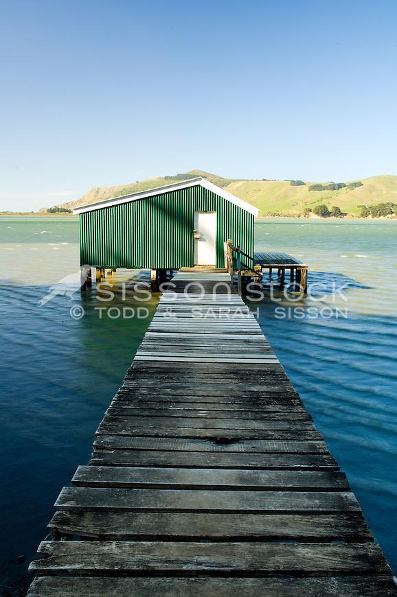 Wooden boardwalk and green corregated iron boatshed on the Otago Peninsula, South Island, New Zealand - stock photo, canvas, fine art print