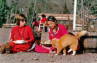 Wasco, Oregon, February 1984:  Two women disciples of Bhagwan Rajneesh, having a meal together outdoors in Rajneeshpuram. Rajneeshpuram, was an intentional community in Wasco County, Oregon, briefly incorporated as a city in the 1980s, which was populated with followers of the spiritual teacher Osho, then known as Bhagwan Shree Rajneesh. The community was developed by turning a ranch from an empty rural property into a city complete with typical urban infrastructure, with population of about 7000 followers.