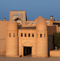 General view of main gate of Ichan-Kala, Ota Darvoza (Father Gate), with the Muhammad Rakhim-khan II Madrasah, 1871, in the background, Khiva, Uzbekistan, pictured on July 6, 2010, at sunset. Khiva's old city, Ichan Kala, is surrounded by 2.2 kilometres of crenellated and bastioned city walls. The main gate today is the restored western Ota Darvoza (Father Gate). Khiva, ancient and remote, is the most intact Silk Road city. Ichan Kala, its old town, was the first site in Uzbekistan to become a World Heritage Site(1991). Picture by Manuel Cohen.