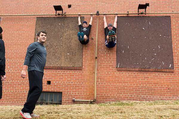 December 22, 2014. Lexington, North Carolina.<br />  (left to right) Frank Callicutt looks on as Mayor Newell Clark and his cousin Stan Lanier do leg lefts on the wall of the abandoned Lexington Furniture factory.<br />   Newell Clark, the 43 year old mayor of Lexington, NC, leads a group of friends and colleagues on a 4 times a week exercise routine around downtown. The group uses existing infrastructure, such as an abandoned furniture factory, loading docks, stairs, and handrails to get fit and increase awareness of healthy lifestyles in a town more known for BBQ.<br /> Jeremy M. Lange for the Wall Street Journal<br /> Workout_Clark