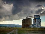Idaho, Eastern, Tetonia. Grain elevators under stormy skies.