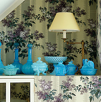A collection of American milk glass and its French couterpart 'opaline de foire' are displayed against a fabric-covered wall