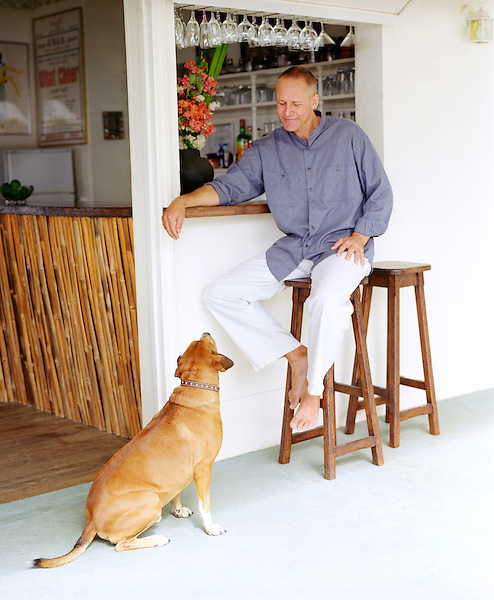 CASTLE BRUCE, DOMINICA: Beau Rive owner and British ex-pat Mark Steele plays with Winston the dog outside the roof top terrace bar at Beau Rive Hotel in Dominica. Beau Rive is situated 240 feet above sea level on the East (Atlantic) coast between the villages of Castle Bruce and Sineku. The hotel is nestled into a hillside amid three acres of tropical gardens and forest, with a dramatic view of the ever-crashing waves at Anse Francais and Wakaman Point. Dominica.
