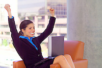 Beautiful woman working on laptop computer with her arms in the air
