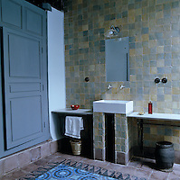 The bathroom is tiled with a palette of smokey blues and mauves