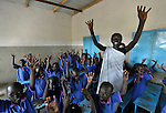 Students sing a song with hand motions in a Catholic school in Malakal, Southern Sudan. Encouraging them is their teacher, Regina John Thabo, who is studying to be a better teacher in a program sponsored by Solidarity with Southern Sudan, an international network of Catholic groups supporting Southern Sudan with educational personnel and prayer.