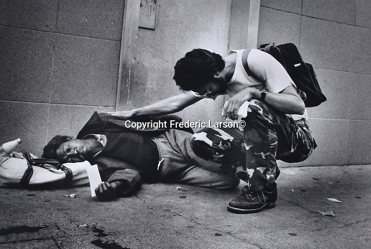 A man kneels down beside another person who was sleeping on the sidewalk and says a prayer on his behalf and then puts a prayer in the persons and in walks away.