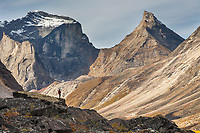 Hiker on a large boulder in Arrigetch Creek, morning light on Xanadu (left) and Arial peaks, Arrigetch Peeks, Gates of the Arctic National Park, Alaska.