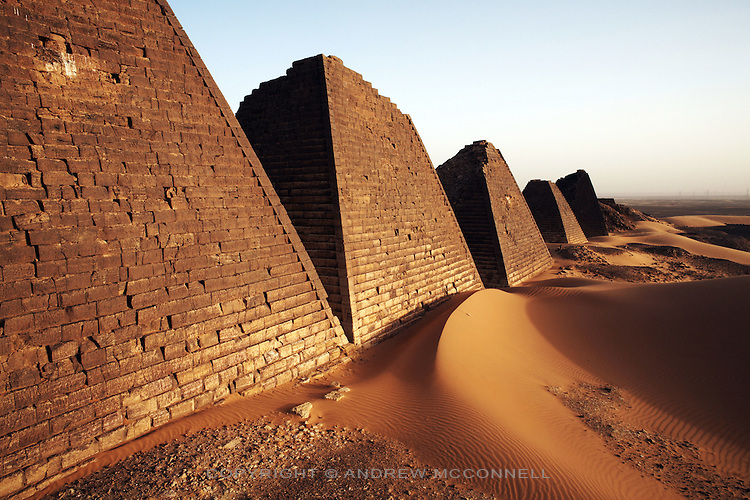 The pyramids of Meroe, Sudan's most popular tourist attraction, pictured on Saturday, March 31, 2007. The old Kushite capital of Meroe contains around 100 pyramids in various states of preservation. The earliest date from around the 8th century BC, Kings and Queens continued to be buried here until the fall of Kushite rule in the 4th century AD...The ancient kingdom of Kush emerged around 2000 BC in the land of Nubia, what is today northern Sudan. At their height the Nubians ruled over ancient Egypt as the 25th Dynasty between 720 BC and 664 BC (known as the Black Pharaohs) and saw their borders reach to edges of Libya and Palestine. The Kushite kings saw themselves as guardians of Egyptian religion and tradition. They centered there kindgom on the Temple of Amun at Napata (modern day Jebel Barkal) and brought back the building of Pyramids in which to inter their kings - there are around 220 pyramids in Sudan, twice the number in Egypt. After Napata was sacked, by a resurgent Egypt, the capital was moved to Meroe where a more indigenous culture developed, Egyptian hieroglyphics made way for a cursive Meroitic script, yet to be deciphered. The Meroitic kingdom eventually fell into decline in the 3rd century AD with the arrival of Christianity.