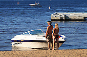 a young couple park their motorboat on beach at  Lake Maskinonge,