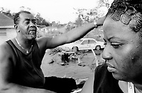 USA. Louisiana. New Orleans. Orleans Parish. 9th Ward area. A month after the storm, a black couple comes back for the first time and have a look at the devastated area. Their house is totaly destroyed and they will never live here again. The wife is extremely sad. The 9th Ward used to be the living place of the black (afro-american) community. Aftermath of hurricane Katrina. The area is empty and all its inhabitants have left the town. The people could no longer and ever live again in the houses because of the destructions due to the floods and the water. The entire area needs to be bulldozed before any new construction can be built.  Destruction of the urban american way of life. © 2005 Didier Ruef