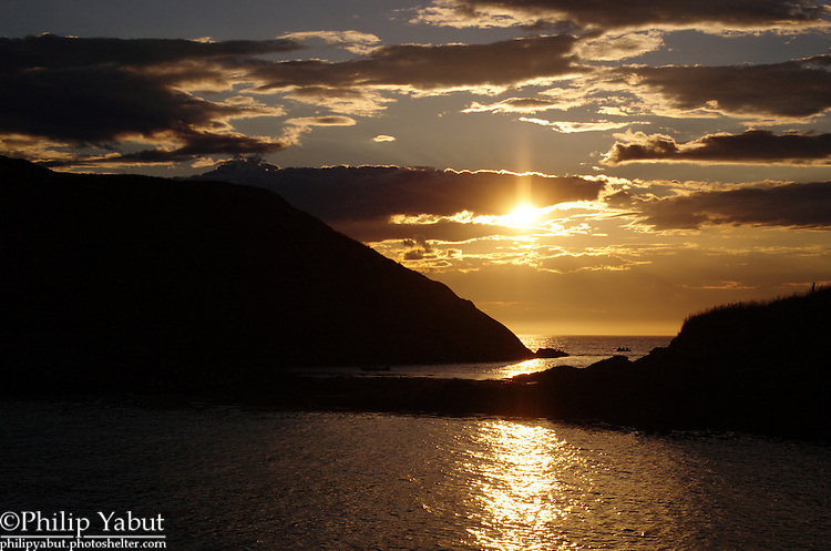 The sun begins to set behind Manana and Smuttynose Islands, as seen from Monhegan Island, Maine.