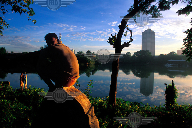 A man sits in the dawn light beside a lake in the centre of Sri Lanka's capital city.