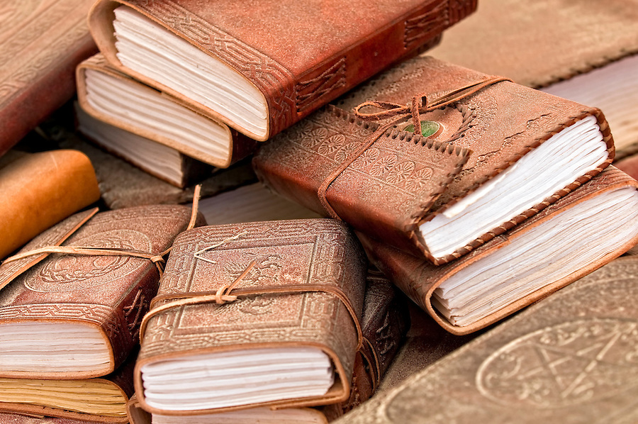 Pile of old books with leather covers, covered in dust and sand.