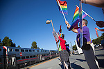 Local advocates wave flags in celebration of the Supreme Court's overturn of the Defense of Marriage Act (DOMA) and California's Proposition 8 as Caltrain pulls into the Mountain View station June 27. The decision opens the doors for the issuance of marriage licenses for same-sex couples in California.