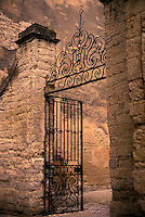 Decorative wrought iron gate and stone wall at entrance to courtyard, ozes, Provence, France