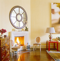 A circular mirror hangs above the living room fireplace creating the illusion of a large porthole window