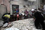 Syrians remove the debris following an air strike by government forces on the al-Mowasalat neighbourhood of the northern Syrian city of Aleppo on September 20, 2015. Photo by Ameer al-Halbi