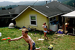 From left, Sheldon Eilers, 10, and Alexa Taylor play in the backyard of a Scotia, CA home on Tuesday, June 27, 2006. The town of Scotia in Northern California is a company town owned by the Pacific Lumber Company (PALCO), but that will change as the company will begin to sell the town. (Photo by Max Whittaker for The New York Times)<br />