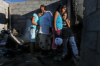 06/01/2010..The Vazquez Ledezma family embrace as they stare at the remains of their two bedroom home situated on the 16 de Septiembre suburb of Ciudad Juarez. Mrs. Vazquez went to protest the detention of her 24-year-old son, who she alleges was wrongfully accused of murder and was being held at the municipal prison. When she returned home, she saw two young men run out of the back of the house as the flames began to engulf her home.