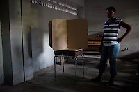 A poll worker watches as ballot boxes are assembled before hte opening of a voting station for presidential and legislative elections on November 28, 2010 in Port-au-Prince, Haiti.