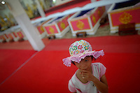 A little girl stand by coffins ready for a ritual at Wat Prommanee temple in Nakhon Nayok province May 28, 2011. Hundreds of Buddhist believers pay small fee to lay in nine pink coffins at 9:09 am and 1:09 pm every day in Wat Prommanee temple during its unusual daily resurrection service that they believe will wash away bad luck and prolong life.      REUTERS/Damir Sagolj (THAILAND)