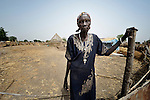 Bruna Maloal, a 63-year old Roman Catholic catechist, stands at the gate to her home in Abyei, a town at the center of the contested Abyei region along the border between Sudan and South Sudan. Her home was looted and burned in 2011 when soldiers and militias from the northern Republic of Sudan swept through the area, chasing out Maloal and tens of thousands of others. Maloal and a handful of other residents returned to the town in 2012 after northern combatants withdrew. Although Ethiopian peacekeepers patrol the region, renewed attacks by northern-backed Misseriya militias in 2013 have Maloal and others worried. The African Union has proposed a new peace plan, including a referendum to be held in October 2013, but it has been rejected by the Misseriya and Khartoum. The Catholic parish of Abyei, with support from Caritas South Sudan and other international church partners, has maintained its pastoral presence among the displaced and assisted them with food, shelter, and other relief supplies. Yet the parish priests have not officially returned to Abyei, remaining with most Abyei residents in Agok, some 25 kilometers to the south. Every Sunday a priest comes to celebrate Mass in Abyei, with church members gathering under a tree outside the desecrated sanctuary.