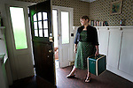 A blond woman wearing a green dress in a retro house holds her suitcase at the front door.