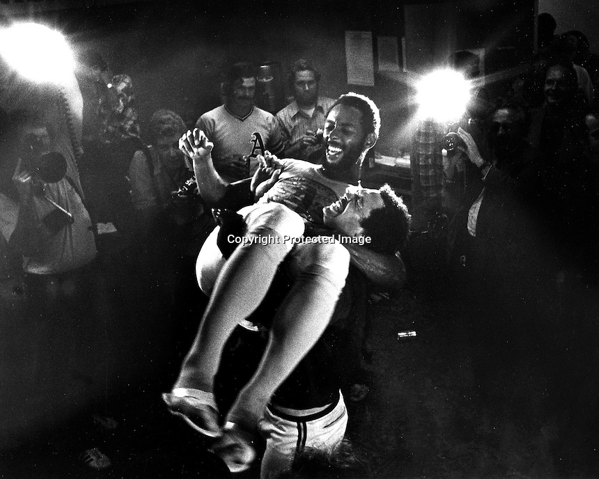 Oakland A's celebrate in the locker room after cinching the 1974 American League championship.<br />A's outfielder Billy Northis hoisted up by slugger Reggie Jackson. (photo 1975/Ron Riesterer)