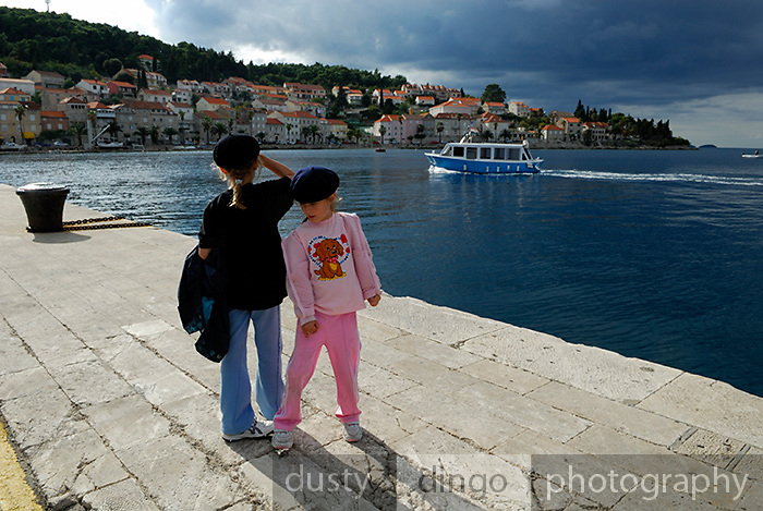 Two children (9 years old, 5 years old) standing at waterfront, Korcula old town, Island of Korcula, Croatia.