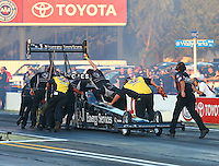 Feb 6, 2015; Pomona, CA, USA; Crew members and a couple members of the Safety Safari push NHRA top fuel driver Dave Connolly back after his burnout during qualifying for the Winternationals at Auto Club Raceway at Pomona. Mandatory Credit: Mark J. Rebilas-
